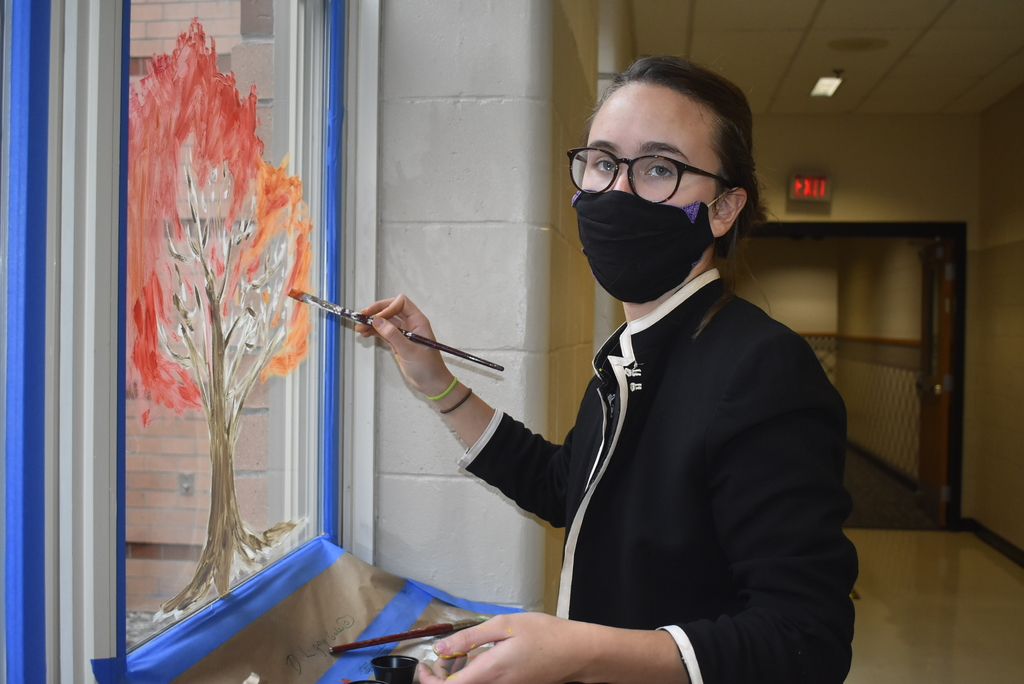 Student painting window